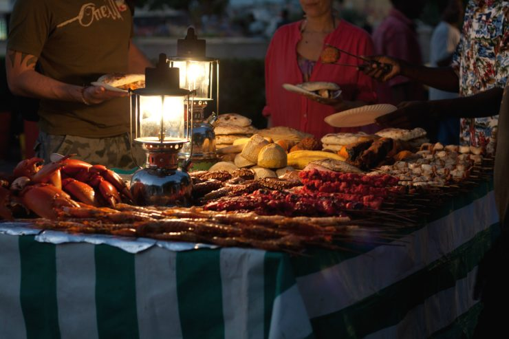 street-food-repas-barbecue-rue-nourriture-bouffe-plat-exterieur-table-lampe-nuit-afrique-mains-zanzibar