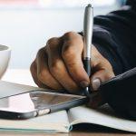 main-noire-ecriture-cahier-stylo-blogging-iphone-smartphone